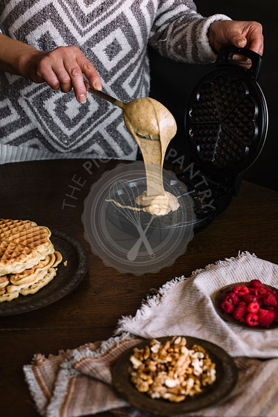 WOMAN IS POURING DOUGH ON WAFFLE MAKER