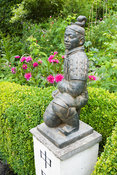 Statue of a terracotta warrior from Xi'an crouching on a pedestal marked with the word 'China', framed by clipped box hedge b...