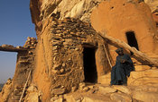 Hogon, spiritual leader, smoking a pipe in his carved cliff home, Ende village, Dogon Country, Mali