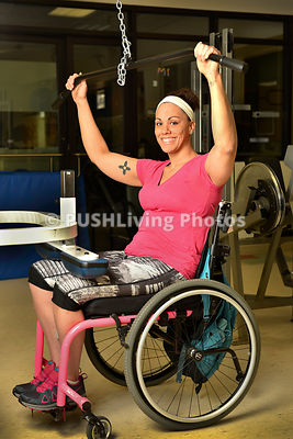 Young woman using a wheelchair exercising in a gym