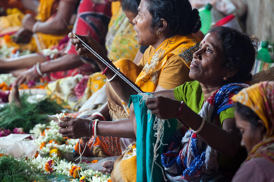 Women string flowers at the Howrah Flower Market, Kolkata, India. It's the largest flower market in Asia.