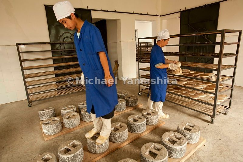 Puer tea is steamed and pressed into flat cakes as it has been for hundreds of years. Here at Yiwu's Bao Pu Shan tea factory,...