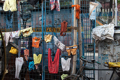 Laundry hangs drying on a fence near a homeless camp on Strand Road, Kolkata, India.