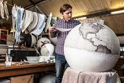 UK - London - Peter Bellerby of Bellerby and Co. Globemakers adds detail to a large globe