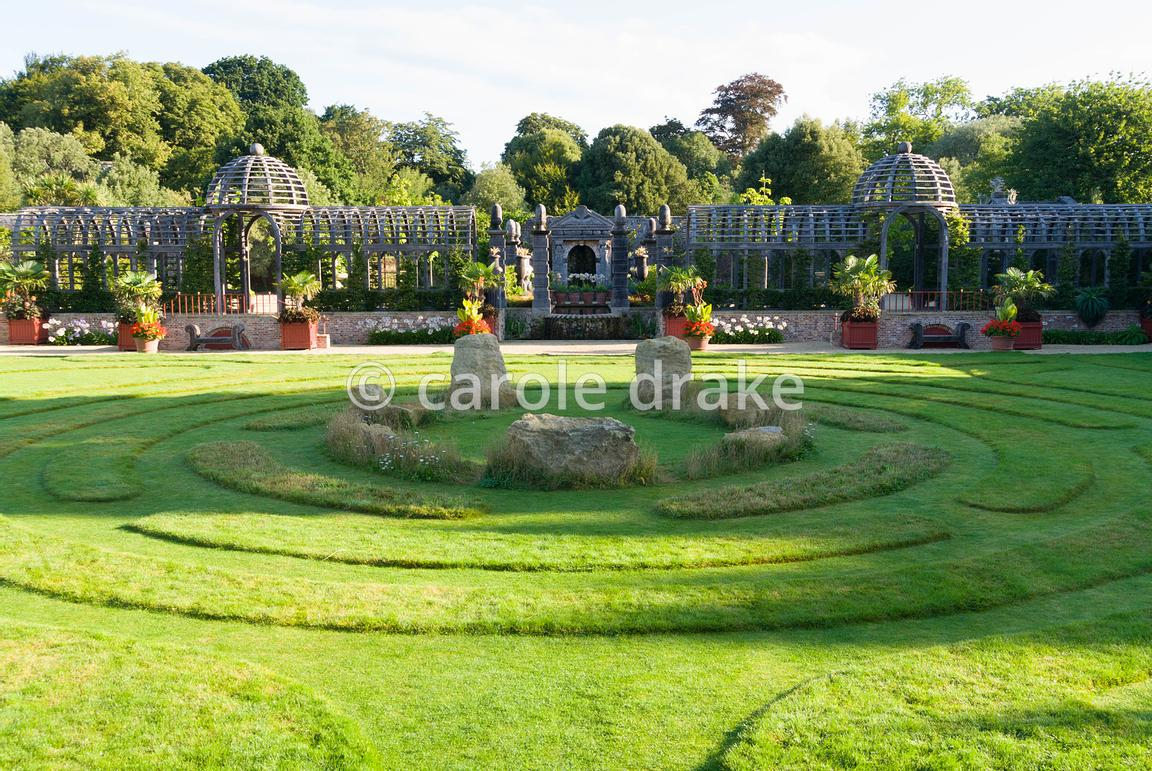 Double domed pergola in oak spans the garden dividing upper gravelled courtyards from the lower lawn featuring maze and centr...