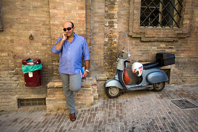 Italy - Urbino - A man talks on his mobile telephone