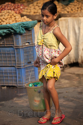 A girls carries water in a metal bucket in Newmarket, Kolkata, India.