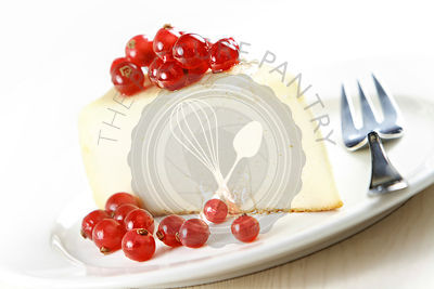 Cheesecake with red currant on white plate