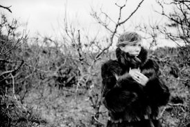 Woman in fur among bare trees #3