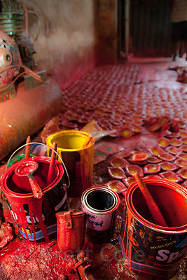 Workers paint small ceramic dishes at a workshop in Kumartoli (Potter's Town), Kolkata, India.