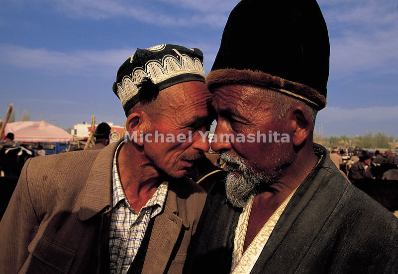 Men bargain in Kashgar market, Xinjiang, China. Bargaining takes place the usual way: head to head.