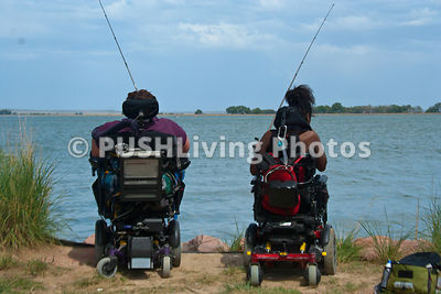 Two people in wheelchairs fishing on the edge of a lake