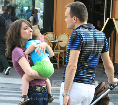 Young couple with toddler, talking on street in Paris, France