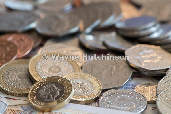Piles of Great British currency including cash and coins in sterling.