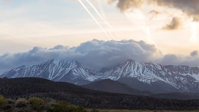Medium Shot: Snow Capped Eastern Sierra Mountains Holding Back a Forceful Cumulonimbus Weather System Coming in From the Paci...
