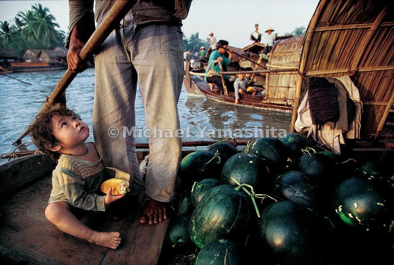 A young son trusts his father will not tip the boat at the floating market in Phung Hiep.