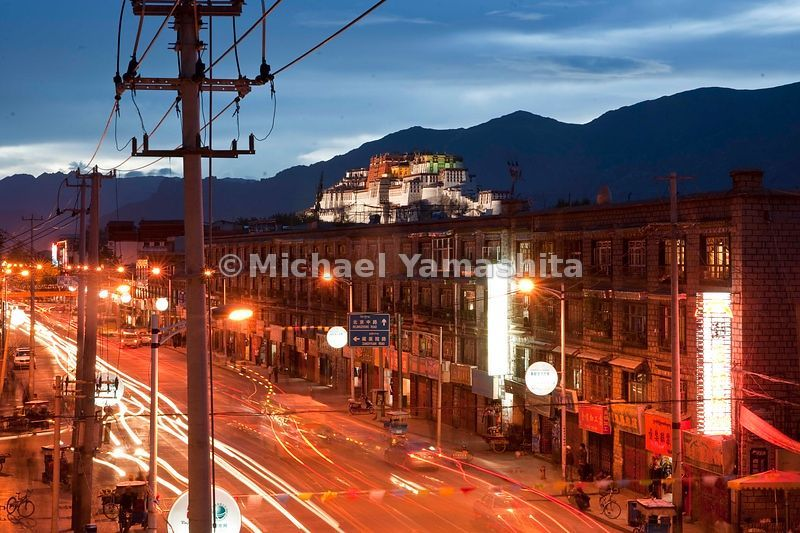 Viewed from the city of Lhasa, with its telephone lines, electric lights and traffic, the Potala Palace is brought back into ...