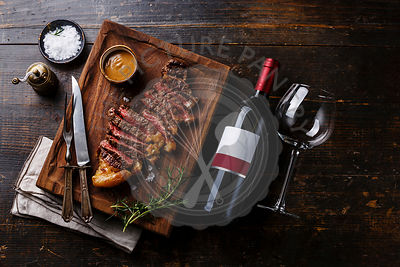 Grilled Steak Striploin with Pepper sauce and bottle of Red wine on wooden background