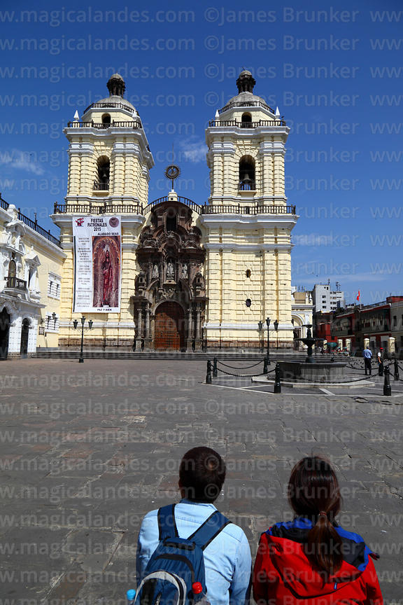 Asian tourists relaxing in square in front of San Francisco church, Lima, Peru