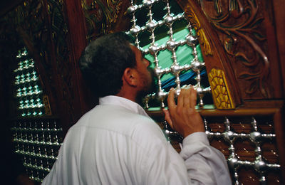 man kisses the shrine in Karbala, Iraq