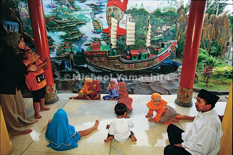 Children take their lessons in Koran school against a backdrop of one of Zheng He's (or Cheng Ho, as he is known here) treasu...