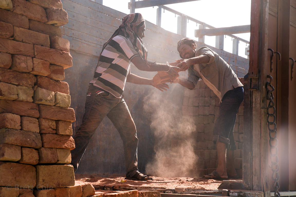 Men unload bricks from a truck at a construction site, Pushkar, Rajasthan, India