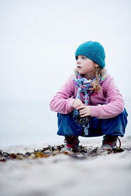 Little Danish girl in a blue hat at the beach in autumn 12