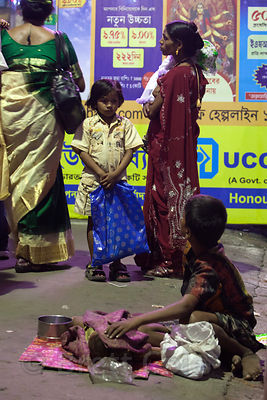 A girl from a middle-class family looks at a girl living on the street in Gariahat, Kolkata, India.