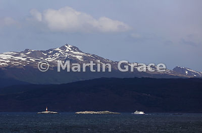 The Beagle Channel near Ushuaia, with a lighthouse and a tourist boat, Tierra del Fuego, Argentina