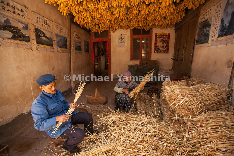 Time for work: Husband and wife are equally intent on binding bundles of Mung beans in the living room of their home near Dal...