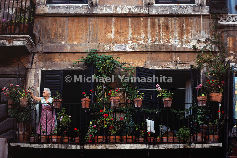 A woman tends to her flowers on her deck in Piazza Navona. Rome, Italy, 1988.