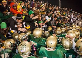 Iowa City West players crowd around the Boot which they bested cross-town rivals Iowa City High to win 44-0 Friday night at I...