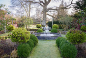 Formal garden with clipped evergreens including standard Cupressus macrocarpa 'Goldcrest', a central pond and a border of rop...