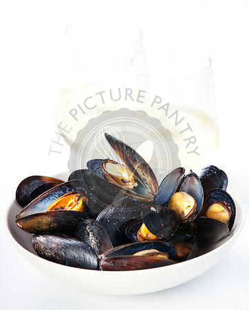 Mussels and clams served in white bowl with glasses of white wine