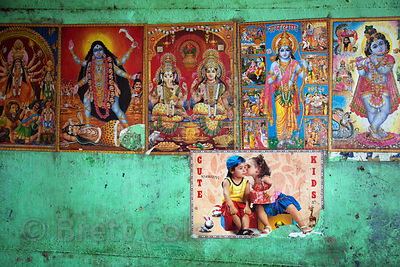 Religious figures and Western posters on a wall at the Howrah Flower Market, Kolkata, India.