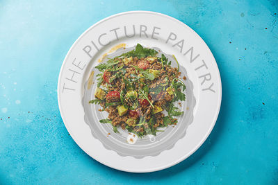 Salad with quinoa, tomato, avocado, spinach and arugula on white plate on blue background