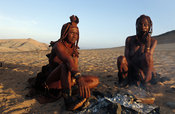 Himba women smoking a pipe at a camp fire, Kunene region, Kaokoland, Namibia
