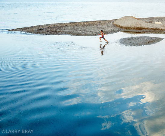 A boy running in the sea with clouds reflected in the water in Kalives, Crete