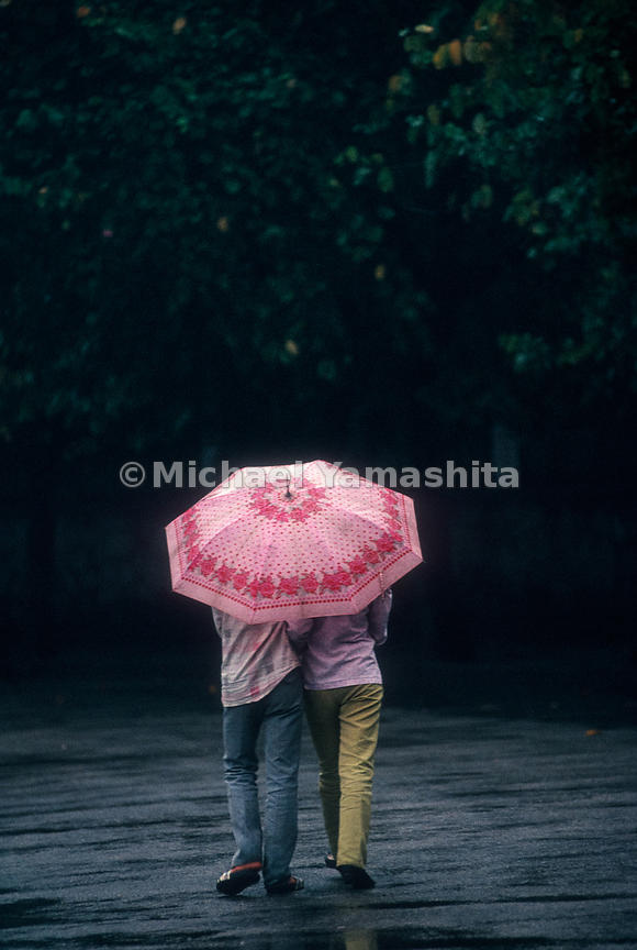 Pair sharing a pink umbrella..China