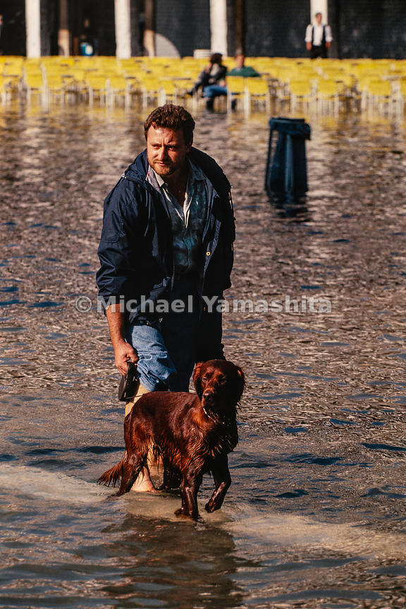 A man and his dog take a walk during the acqua alta in St Mark's Square. Venice, Italy, October, 1993.