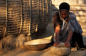 Swazi woman grinding maize outside her beehive hut, Mantenga village, Swaziland