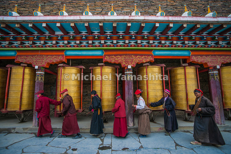 Buddhist faithful at the Segyagu Meditation Center perform the Kora, circumambulating the temple, turning huge prayer wheels as they go, to insure good karma.