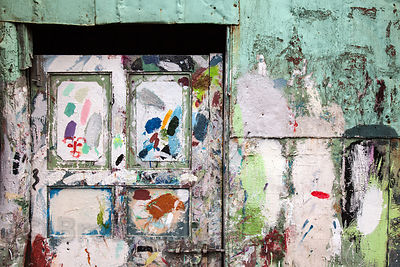 A delightfully weathered door splashed with paint on a street in the Dharavi slum, Mumbai, India.