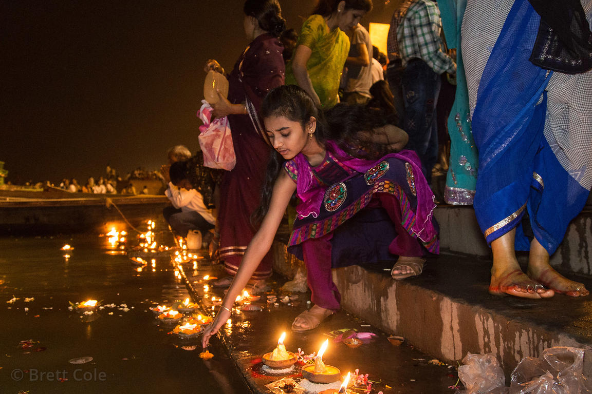 A girl releases a candle onto the Ganges River during Ganga Aarti at Dashashwamedh Ghat, Varanasi, India