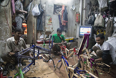 Workers at a bicycle assembly shop in the Cycle Market in Delhi, India