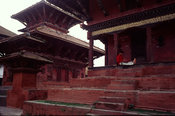 A man sits amidst the palaces in Durber Square, Kathmandu, Nepal