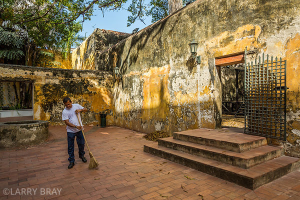 Man sweeping in old courtyard at Museum in Cartagena, Colombia, South America