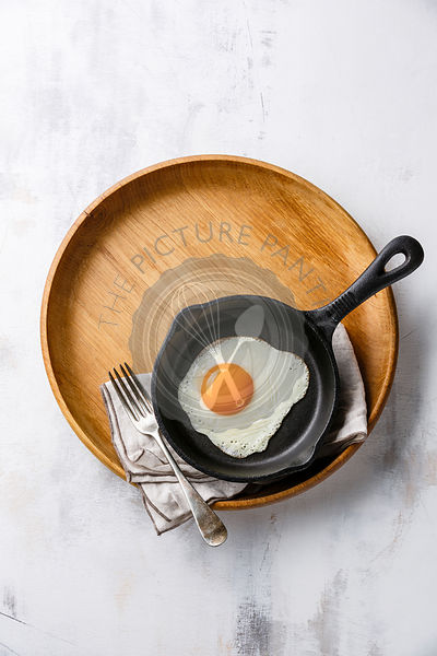 Breakfast with fried egg on iron pan on wooden tray on white background copy space