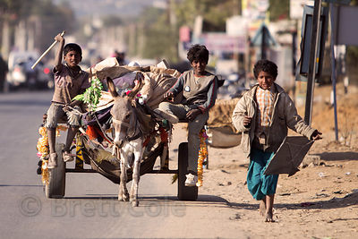 A group of boys bring trash (recycling) they've collected from a rural village to be redeemed in town, via their donkey cart,...