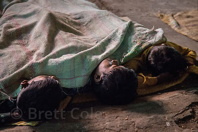 Young market laborers sleep on-site at a warehouse in Newmarket, Kolkata, India.